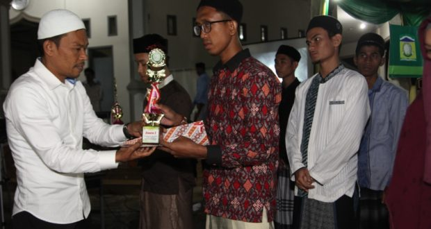 BUPATI Aceh Besar Mukhlis Basyah SSos menyerahkan piala kepada juara Musabaqah Qiraatul Kutub Se-Aceh Besar Tahun 2016 pada penutupan acara itu di Kompleks Dayah Darul Amal, Lubok, Kecamatan Ingin Jaya, Aceh Besar, Minggu (25/12/2016) malam.